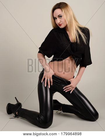 Slender Leggy Girl Blonde In Black Leggings And A Shirt On Her Knees