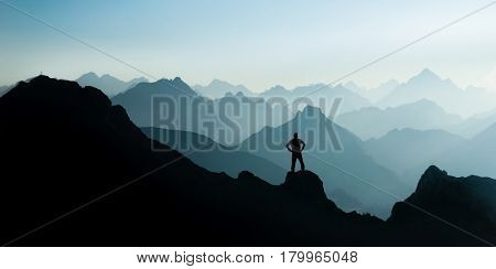 Happy winning success man at sunset or sunrise standing relaxed and is happy for having reached mountain top summit goal during hiking travel trek. Tirol, Austria. Bavaria. Blue and cyan mountain ranges silhouette with bright back light. Summit crosses ar