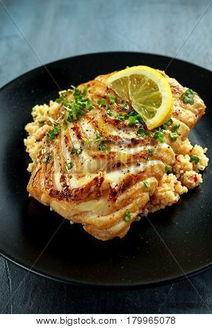 Soy-glazed cod loin fillet with cous-cous salad on black plate.
