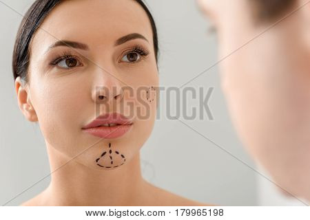 Focus on portrait of serene female with correction marks. She looking at therapeutic