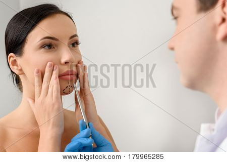 Focus on serene female with correction marks watching at physician. Therapeutic examining chin of girl before operation