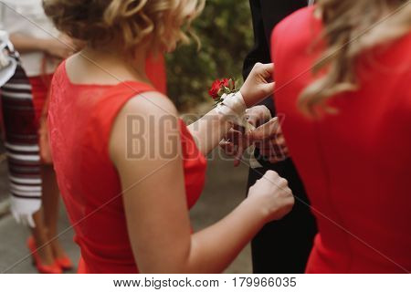 Handsome groom in black suit putting on red roses boutonniere on beautiful blonde bridesmaid in stylish red dress hand closeup