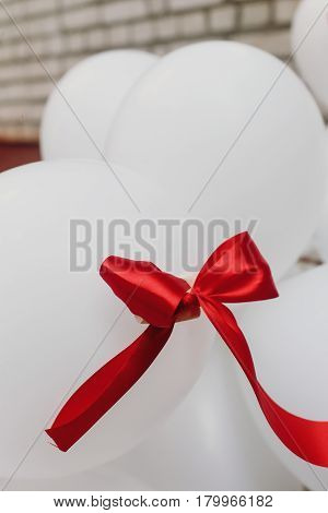 Red ribbon on bunch of white decorative air baloons balloons wedding decor closeup
