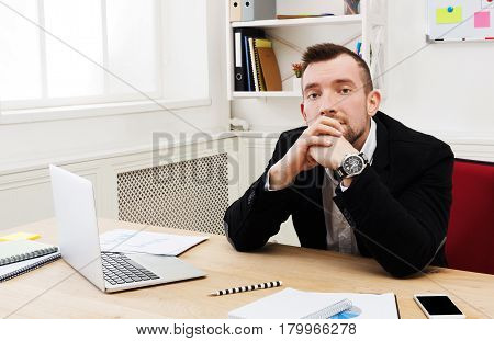 Get the trouble. Upset frustrated businessman sitting at workplace in modern office and thinking about something