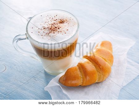 Latte macchiato coffee. Breakfast with coffee and croissant Shallow depth of field