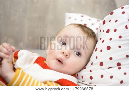 surprised baby lying on the sofa. the child's eyes widened and his mouth opened in amazement.