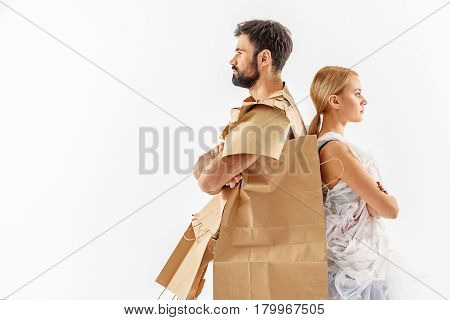 Strong opposition. Serious couple dressed in bags with paper and plastic is standing with their backs to each other. They are looking ahead. Isolated and copy space