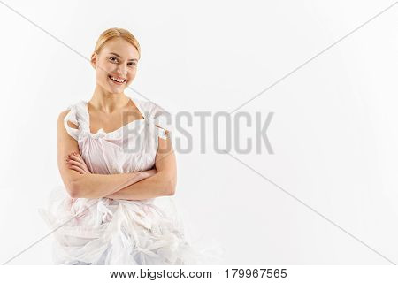 Hilarious woman dressed in plastic bags is crossing hands and looking at camera with smile. Portrait. Isolated and copy space