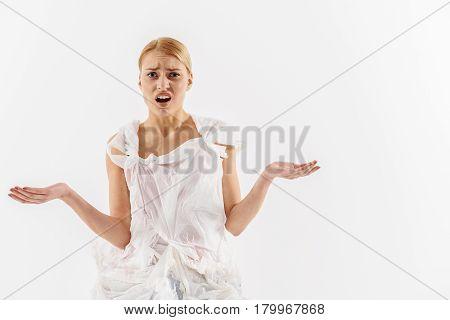 Shocked female person wearing polyethylene packages making helpless gesture. Portrait. Isolated and copy space