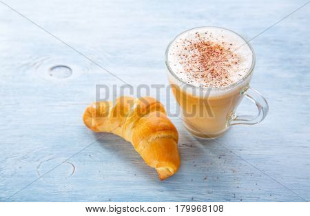 Breakfast with Latte macchiato coffee and croissant.