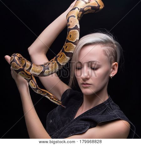 Blond woman with snake on black background