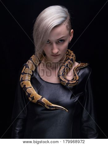 Woman in leather dress and royal python on black background