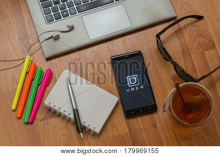 Nitra, Slovakia, april 3, 2017: Uber application in a mobile phone screen. Workplace with a laptop, an earphones, notepad, pen, tea, sunglasses and color markers on wooden background