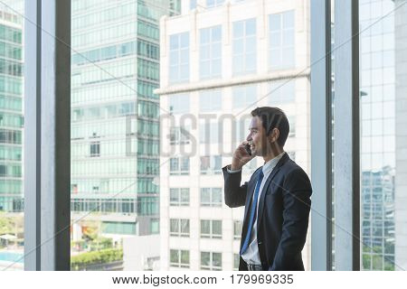 Mature and confident business executive looking looking out of large windows at a view of the city below from the top floor of an office building while talking on his mobile phone