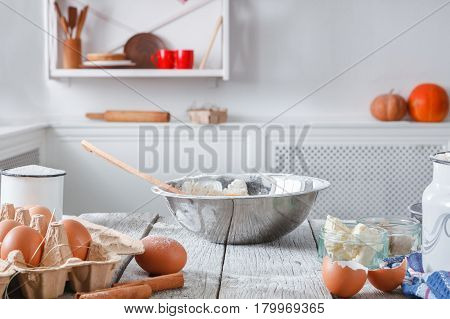 Kitchen utensils, baking ingredients . Products for cooking dough on white wooden table in rustic kitchen, blurred background