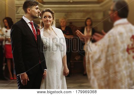 Emotional couple during wedding ceremony handsome happy groom and beautiful bride tearing up during priests speech at wedding ceremony in christian church