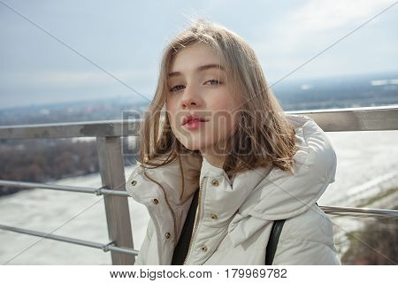 Young Adorable Blonde Teen Girl Having Fun On The Observation Deck With A View Of Cloudy Spring Sky,