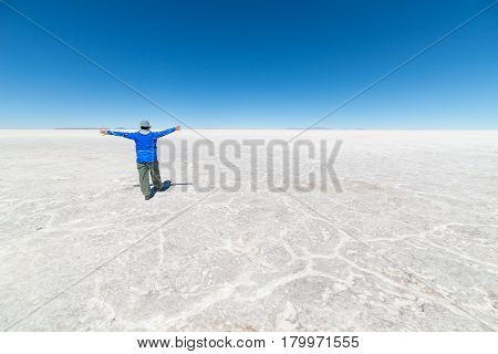 Tourists exploring the world famous Uyuni Salt Flat among the most important travel destination in the Bolivian Andes. Wide angle view clear blue sky.