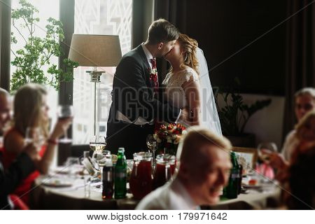 Newlywed Couple Kissing At Wedding Reception In Restaurant, Bride And Groom First Kiss In Front Of F