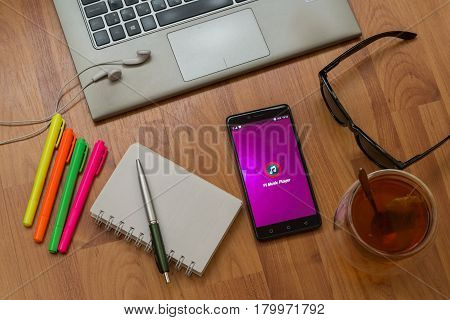 Nitra, Slovakia, april 3, 2017: Pi Music Player application in a mobile phone screen. Workplace with a laptop, an earphones, notepad, pen, tea, sunglasses and color markers on wooden background