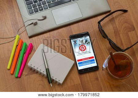 Nitra, Slovakia, april 3, 2017: Pinterest application in a mobile phone screen. Workplace with a laptop, an earphones, notepad, pen, tea, sunglasses and color markers on wooden background