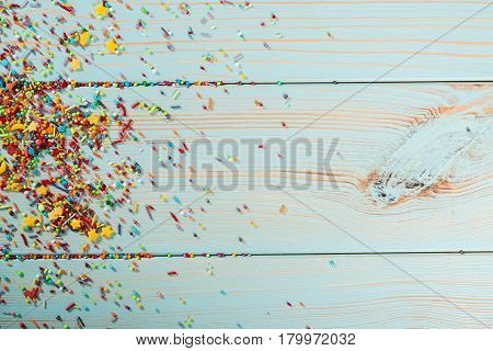 Colorful Sweet Sprinkles On The Wooden Background