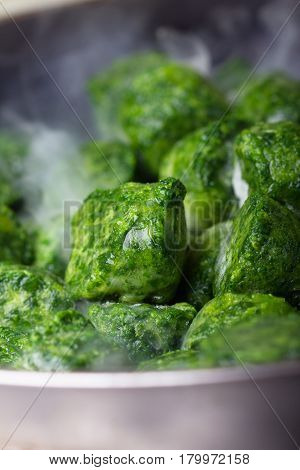 Frozen nice and green briquettes of spinach are being cooked on a pan.