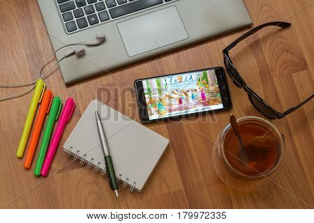 Nitra, Slovakia, april 3, 2017: Ice Age application in a mobile phone screen. Workplace with a laptop, an earphones, notepad, pen, tea, sunglasses and color markers on wooden background