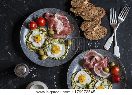 Delicious snack or appetizer - prosciutto zucchini fritters fried quail eggs tomatoes olives on a dark table top view. Mediterranean style food. Flat lay
