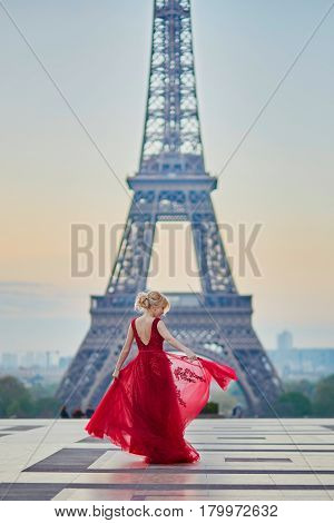 Woman In Long Red Dress Dancing Near The Eiffel Tower In Paris, France