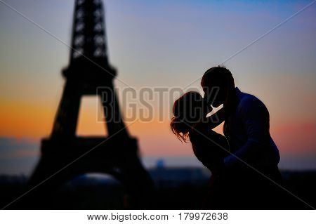 Silhouettes Of A Couple Kissing In Front Of The Eiffel Tower At Sunrise In Paris, France