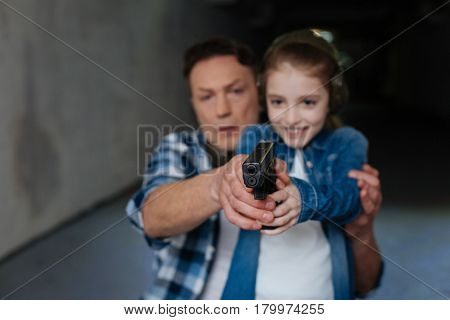 First shooting lesson. Nice exited cute girl holding a handgun and aiming at the target while being directed by her father