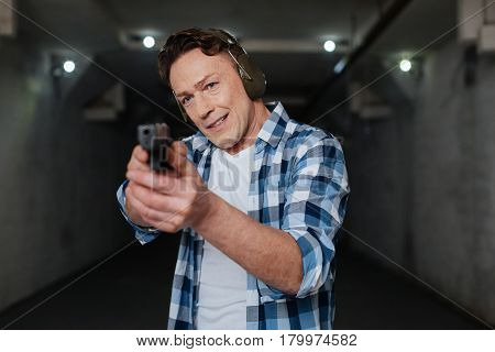 Ready to shoot. Handsome nice pleasant marksman wearing headphones and holding a handgun while preparing to shoot