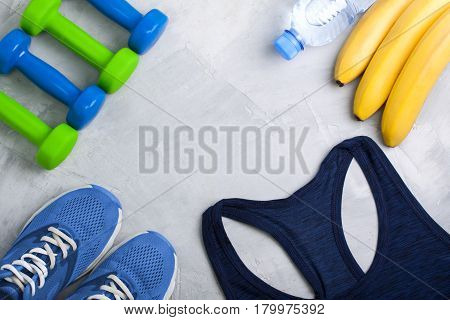 Flatlay sport composition with blue sneakers t-shirt green dumbbells bananas and bottle of water on gray concrete background. Concept healthy lifestyle sport training in gym diet. Horizontal orientation top view place for copyspace.