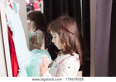 Little pretty girl trying on dress in a fitting room