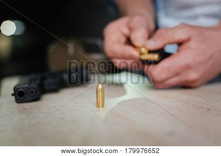 Handgun bullets. Selective focus of a metal handgun bullet standing on the table while being ready to be put into the cartridge clip