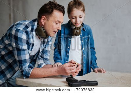 How to reload the gun. Nice positive caring father leaning on the table and putting bullets into the cartridge clip while teaching his daughter how to reload the gun