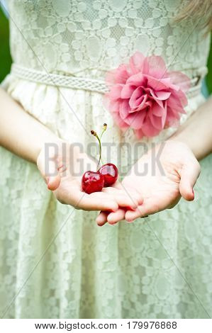 A girl in a summer dress with a flower holds in her hands on the palms two big berries of sweet cherry
