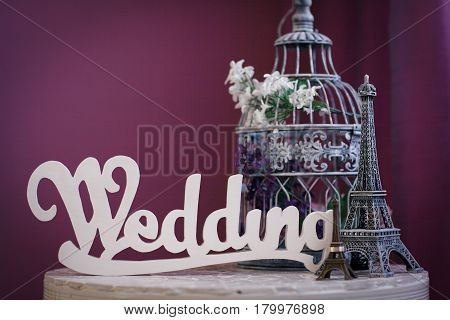 Beautiful wedding composition - the word wedding statuettes of the Eiffel Tower and a cage for birds with flowers stand on a table on a purple background