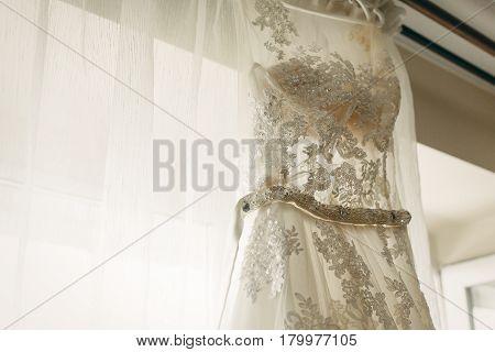 Beautiful White Wedding Dress Hanging Near A Window In Hotel Room, Morning Wedding Preparation, Whit