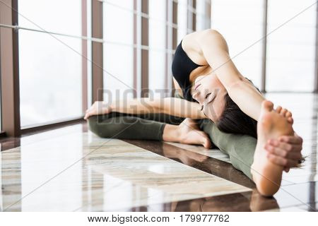 Parivrtta Janu Sirsasana. Beautiful Yoga Woman Practice Near Window Yoga Room Studio Background. Yog