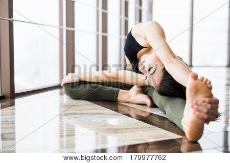 Parivrtta Janu Sirsasana. Beautiful Yoga Woman Practice Near Window Yoga Room Studio Background. Yog