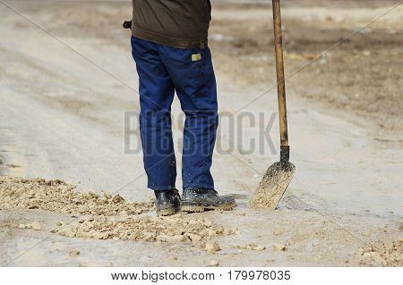 A worker with a shovel strews gravel in pits to level the road.