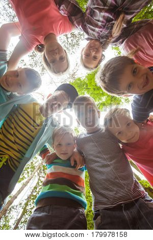 Smiling children standing in a circle and looking down in summer time