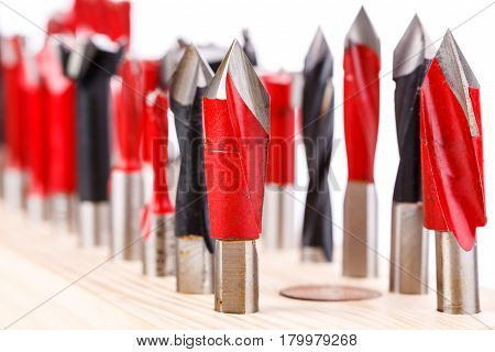 set of different drill bits for wood standing on wooden stand