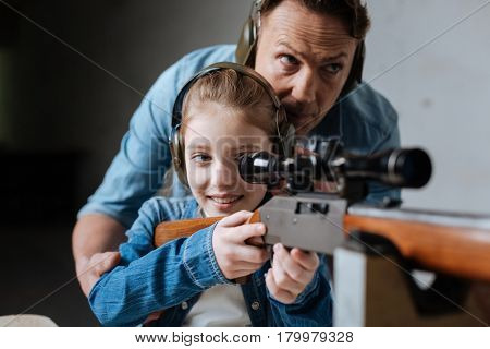 Pleasant activity. Cheerful positive cute girl looking into the optical sight and pulling the trigger while having fun at the shooting gallery