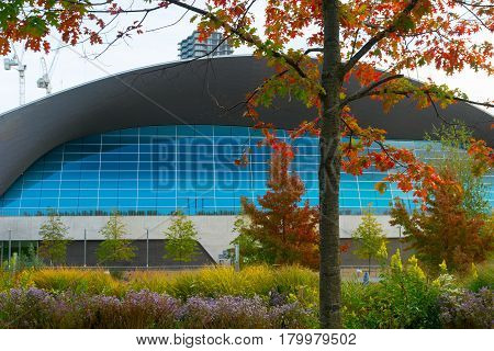 London England - October 17, 2016;  Blue windows and curved architectural roof line London Aquatic Centre Queen Elizabeth Olympic Park contrast with natural autumn colors and bright gardens London UK.