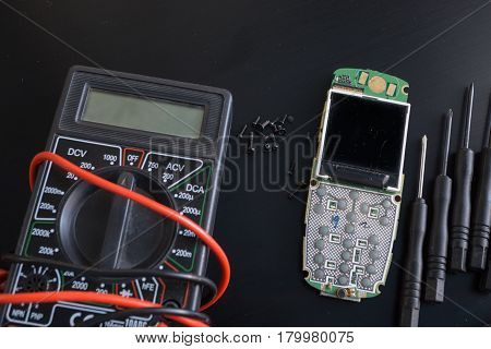 close-up shot of broken cellphone with digital multimeter, screws and screwdrivers on black surface