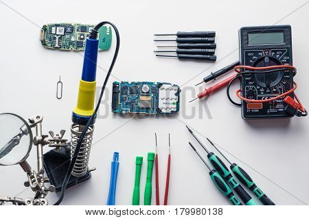 lot of tools for cellphone smartphone repairing fixing including digital multimeter, lot of screwdrivers, soldering iron, pincers, view from the top on white background