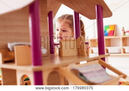 Beautiful little girl playing with a wooden dollhouse